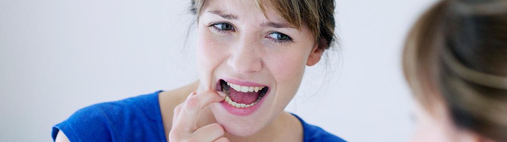femme qui inspecte ses dents dans un miroir pour prévenir les premiers signes de maladie des gencives