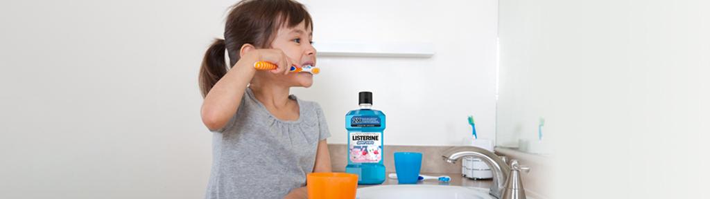 petite fille se brossant les dents, avec un flacon de rince-bouche Listerine sur le comptoir
