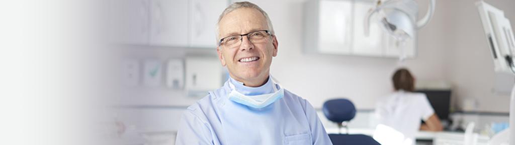 dentiste qui sourit dans son cabinet
