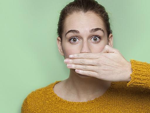 femme qui craint la mauvaise haleine se couvrant la bouche de sa main
