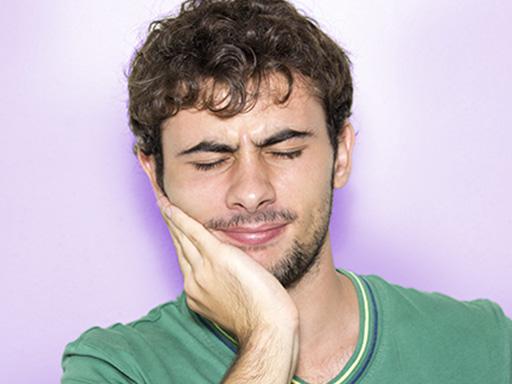jeune homme tenant sa joue dans sa main et souffrant d'un mal de dent